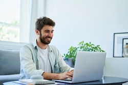 Young happy man typing on laptop while working at home. Good posture concept