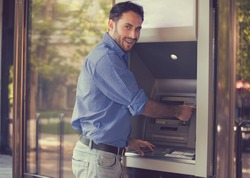 Young happy man using ATM