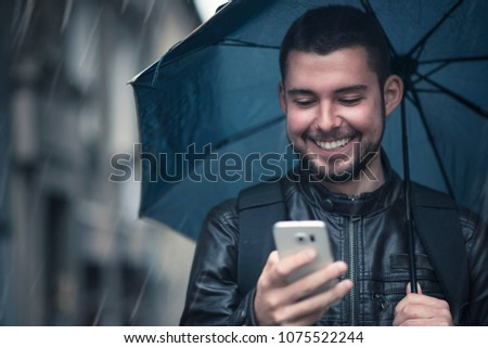 Young happy man using his cell phone, walking the streets on a rainy day and holding an umbrella