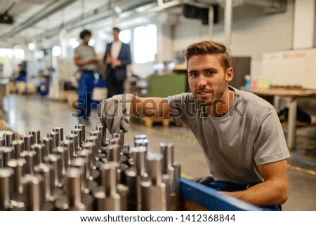 Young happy manual worker analzying quality of steel rods while working in industrial building ad looking at camera.
