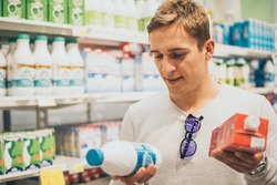Young happy millennial man buying at grocery section of supermarket and choosing products. Comparison of nutritional value and ingredients. Grocery shopping, consumerism and people concept.