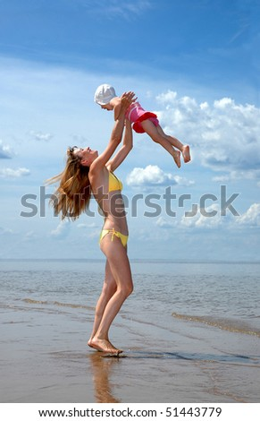 Young happy mother abandons a baby on a beach