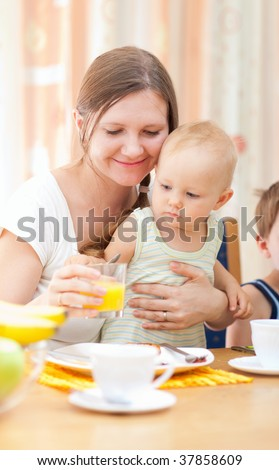 Young happy mother and baby daughter having breakfast together
