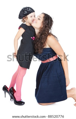 Young happy mother hugging her funny little girl in mummy's shoes over white