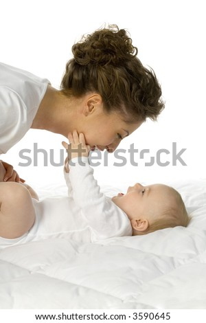 Young happy mother with baby. Woman and baby are lying in bed. Baby is holding mother's  chin. White background