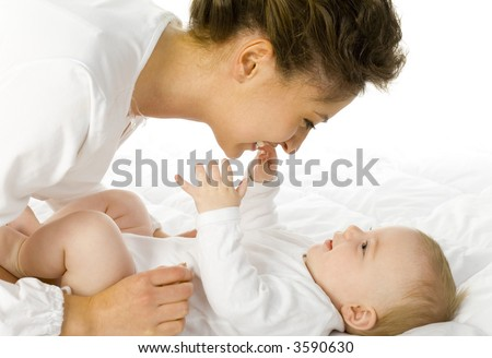 Young happy mother with baby. Woman and baby are lying in bed. baby want to catch mother's face. White background