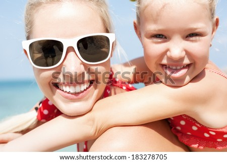 Young happy mother with little girl on her back. Closeup of Happy family having fun at beach in summer
