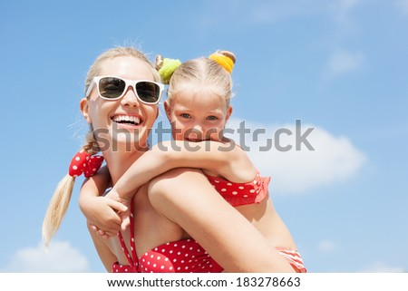 Young happy mother with little girl on her back Happy family resting at beach in summer