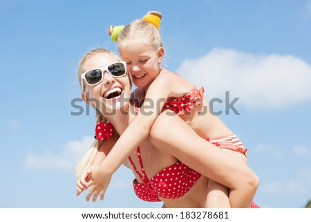 Young happy mother with little girl on her. Outdoors