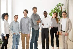 Young happy multiracial professionals or company staff looking at camera smiling, multi-ethnic group of diverse business people standing together, employees posing in office, successful team portrait