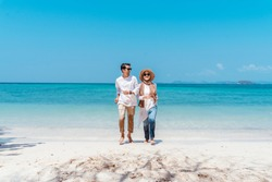 Young happy muslim couple white dress on running seashore. Travel Vacation Retirement Lifestyle Concept. young couple running together on the beach in vacation day. summer time.