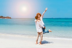 Young happy muslim couple white dress on seashore. Travel Vacation Retirement Lifestyle Concept. young couple hugging on the beach in vacation day. summer time.