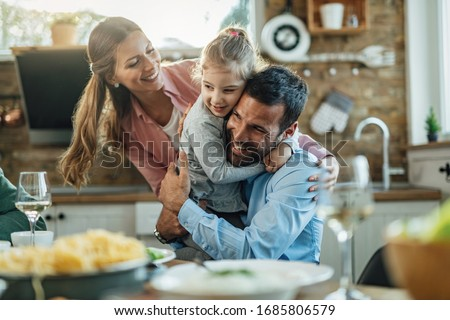 Young happy parents embracing with their small daughter during lunch at dining table.  stock photo