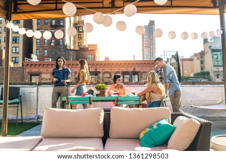 Young happy people having a barbecue dinner on a rooftop in New York - Group of friends having party and having fun #1361298503