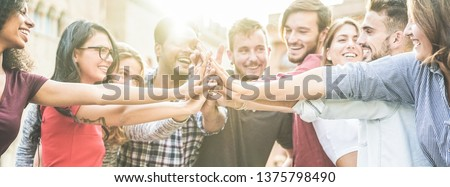 Young happy people stacking hands outdoor - Diverse culture students celebrating together - Youth lifestyle, university, relationship, human resorces, work and friendship concept - Focus on hands