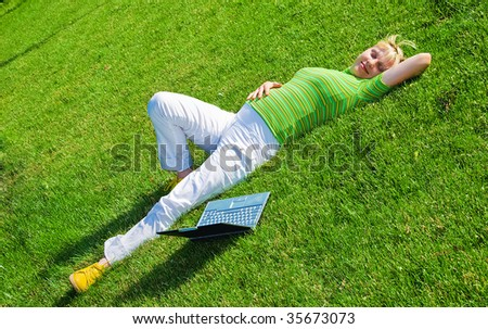 young happy pregnant woman lies on green meadow