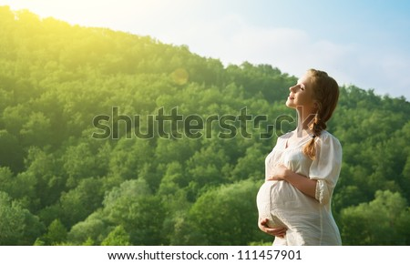 young happy pregnant woman relaxing and enjoying life in nature