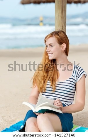 Young happy redhead woman sitting with a book on the beach