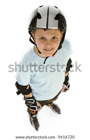 Young, happy roller boy in protection kit standing and looking at camera. High angle view. Isolated on white background.