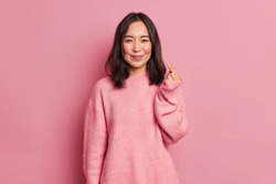 Young happy romantic affectionate Asian woman shapes mini heart gesture with fingers demonstrates sign of love wears oversized jumper isolated over pink studio background. Body language concept