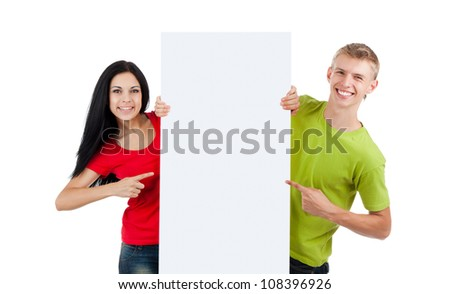young happy smile couple standing hold pointing finger at a blank board, handsome guy attractive girl wear green red shirt, isolated over white background, studio shoot