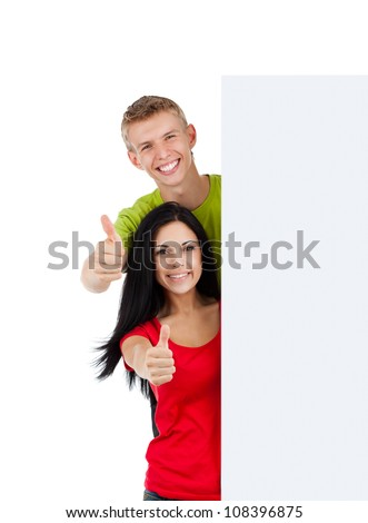 young happy smile couple standing hold pointing thumb up finger gesture at blank board, handsome guy attractive girl wear green red shirt, isolated over white background, studio shoot