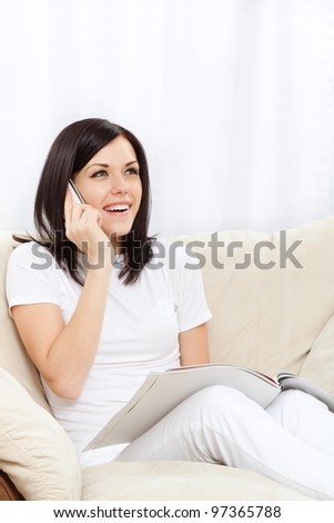Young happy smile woman phone call read magazine on sofa in living room,  at home - indoors, sitting talking using cellphone on chair