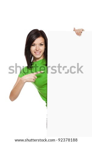 young happy smile woman standing hold pointing her finger at a blank board, attractive girl wear green shirt, isolated over white background, studio shoot