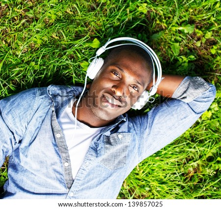 Young happy smiling african american lying on a grass and listens to music in a park