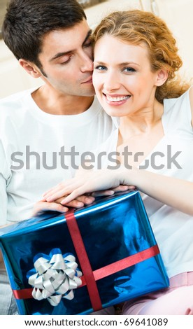 Young happy smiling amorous couple with gift at home