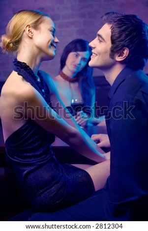 Young happy smiling attractive hugging couple and woman looking at them in nightclub. Focus on couple.