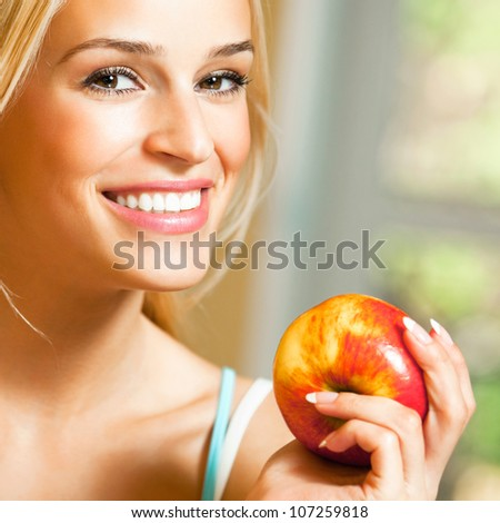 Young happy smiling beautiful blonde woman with apple
