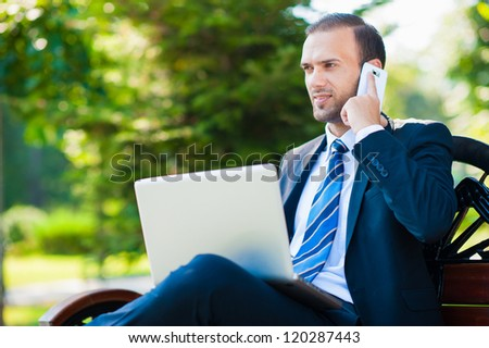 Young happy smiling business man working with laptop and cellphone, outdoors