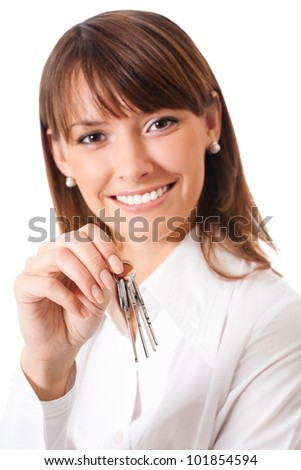 Young happy smiling business woman or real estate agent showing keys from new house, isolated over white background. Focus on keys.