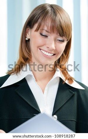Young happy smiling businesswoman working awith documents at office