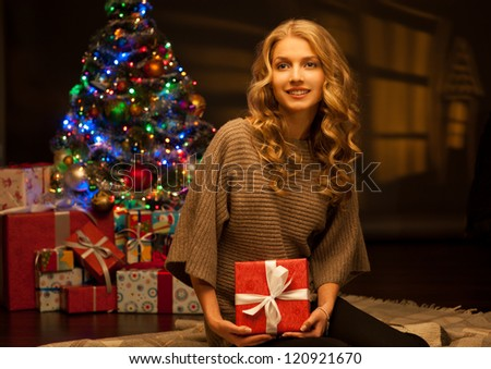 young happy smiling casual woman holding red gift over christmas tree and lights on background. warm light