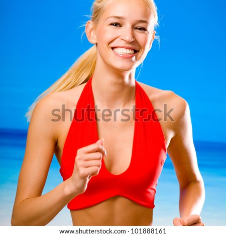 Young happy smiling cheerful blond woman in sports wear running on beach