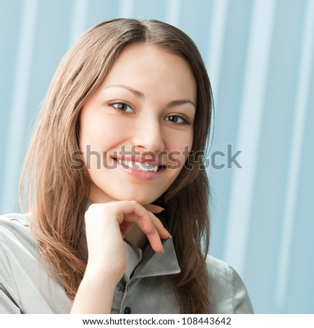 Young happy smiling cheerful business woman at office, with copyspace