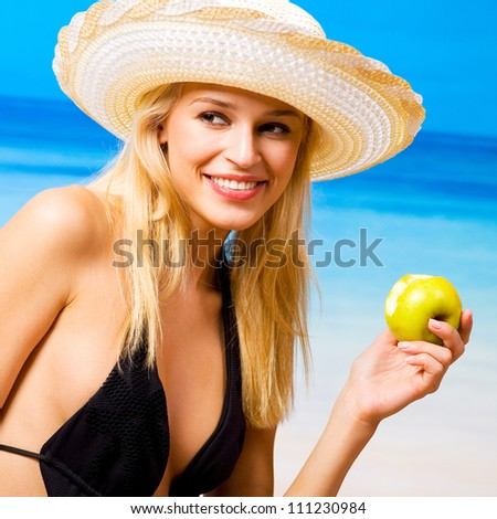 Young happy smiling cherful beautiful woman with apple on beach