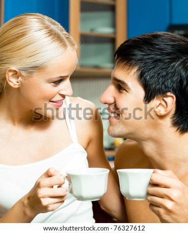 Young happy smiling couple drinking coffee together at home