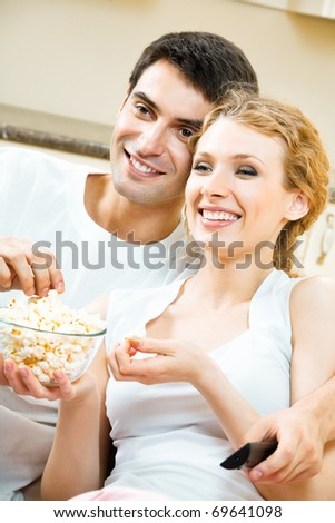 Young happy smiling couple eating popcorn and watching TV together at home