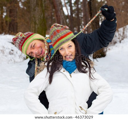 Young happy smiling couple outside during wintertime.