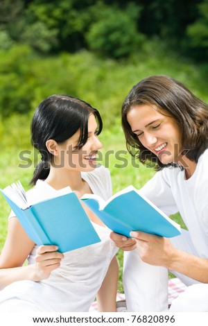 Young happy smiling couple reading a book together, outdoors