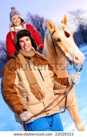 Young  happy smiling couple with horse. Winter sport