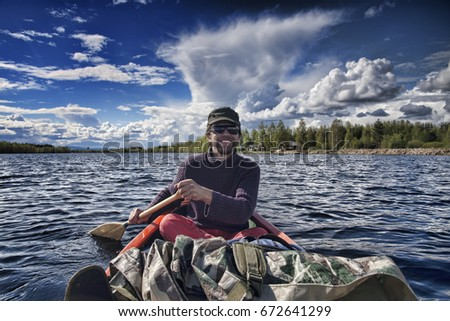 Young happy smiling man in glasses and cap sitting and paddling a canoe on a lake in swedish forest tundra under clouds and blue sky, Sweden