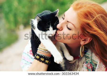 Young happy smiling red-haired girl dressed in hippie bohemian style hugging cat outdoors. Embracing, love, lifestyle.
