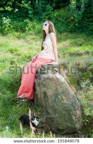 Young happy smiling teenage girl sitting on rock and holding black cat on lead