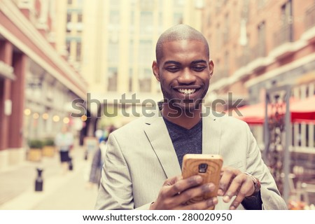Young happy smiling urban professional man using smart phone. Businessman holding mobile smartphone using app texting sms message wearing jacket #280020950