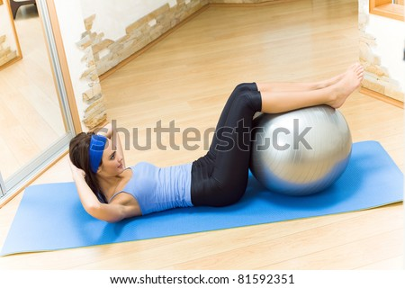 Young happy smiling woman doing fitness exercises with fit ball at home