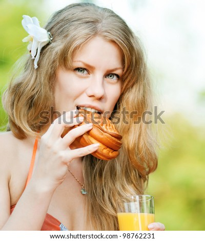 Young happy smiling woman drinking orange juice and eat roll outdoor